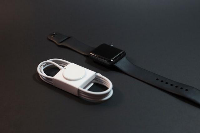 Čierne hodinky a biela nabíjačka na čiernom stole