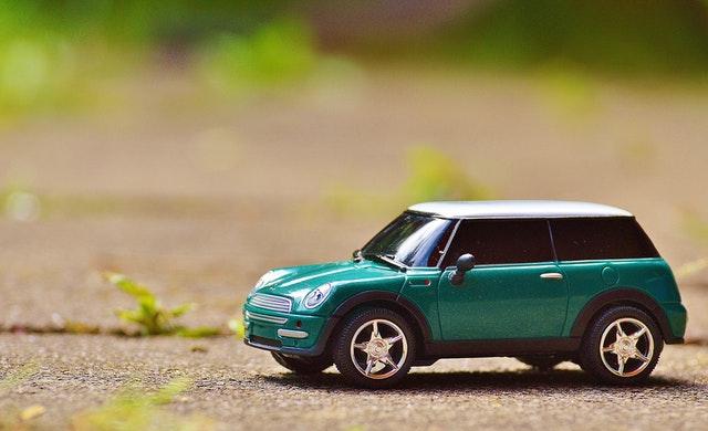 Zelený model auta položený na betónovej ceste