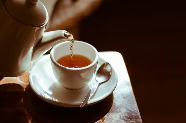 Čaj sa leje z bieleho čajníka do bielej šálky