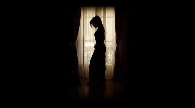 Silueta ženy, ktorá stojí pri tmavých závesoch, pri presklenej časti steny.jpg